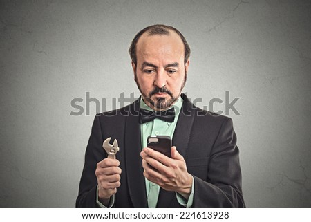 Tools for business solution concept. Businessman executive looking at smartphone holding wrench key instrument in hand on office grey wall background. Face expression emotion leadership determination - stock photo