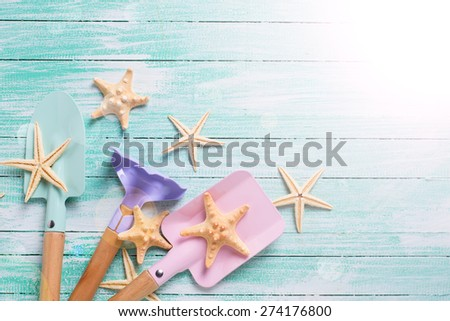 Tools for children for playing in sand  and sea object  in ray of light on turquoise  painted wooden planks. Place for text. Vacation, holiday, summer background.   - stock photo