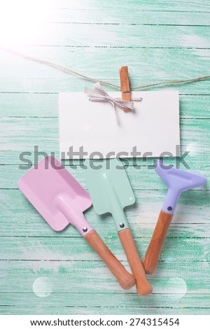 Tools for children for playing in sand and tag on clothes line in ray of light on turquoise  painted wooden planks. Place for text. Vacation, holiday, summer background.   - stock photo