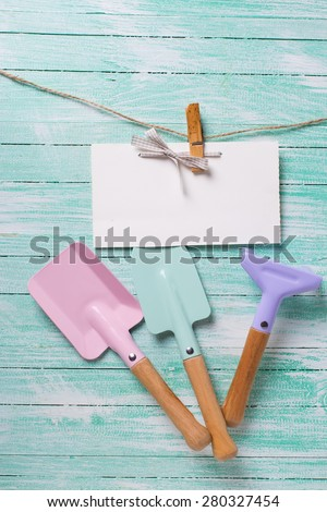 Tools for children for playing in sand and tag on clothes line on turquoise  painted wooden planks. Place for text. Vacation, holiday, summer background.  - stock photo