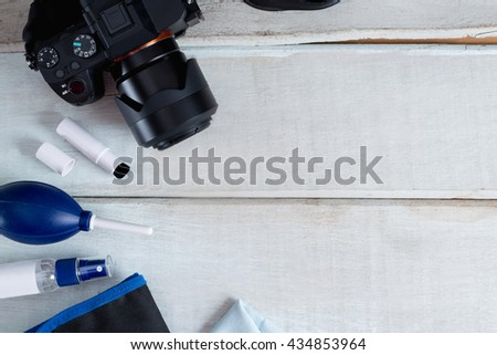 Tools for cleaning camera with dslr camera on white wood background. Selective focus.