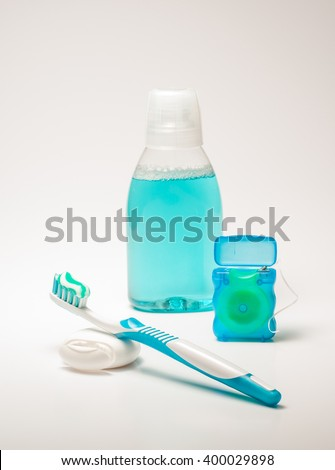 Tools for daily hygiene of the oral cavity - toothpaste, dental floss, tooth brush and mouth rinse. Dental health - oral hygiene objects, isolated on white background. - stock photo