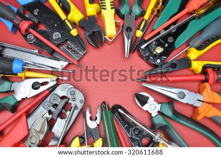 Tools for electrical installation on red metal surface with place on text - stock photo