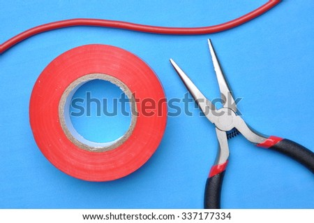 Tools for electrician pliers, insulation tape and cable on blue background - stock photo