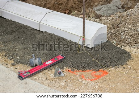 Tools for installing concrete curb stone and string with metal stakes to level at sidewalk construction site. Selective focus. - stock photo