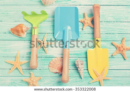 Tools for kids for playing in sand  and sea object on turquoise  painted wooden planks. Place for text. Vacation background. Toned image. - stock photo