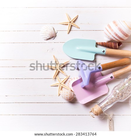 Tools for kids for playing in sand and sea object on white  painted wooden background. Place for text. Vacation background. Square image. - stock photo