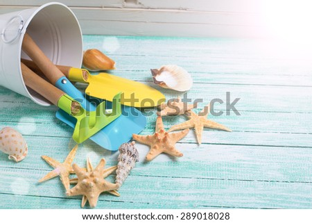 Tools for kids for playing in sand and sea objects in ray of light  on turquoise  painted wooden planks. Place for text. Vacation background. - stock photo