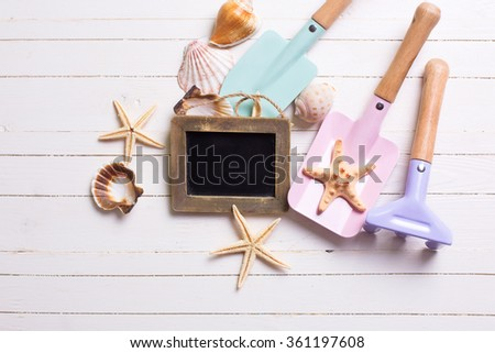 Tools for kids for playing in sand, sea objects and empty blackboard  on white  painted wooden background. Place for text. Vacation background. - stock photo