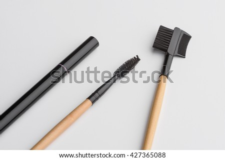 Tools for make-up in macro. Eyelashes brushes and special pencil for eyebrows. Cosmetical equipment for eyes. - stock photo