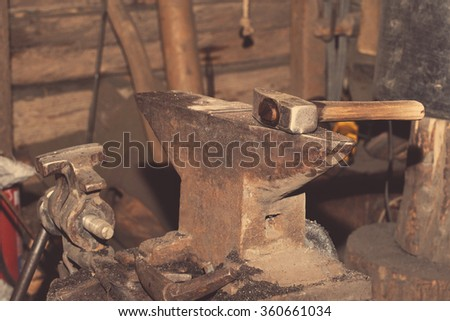 Tools for metal hammer on the anvil in the smithy - stock photo