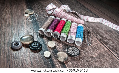 Tools for sewing and handmade tailor or dressmaker. Thread, buttons,  and pins on wooden table. Diversity colors threads, above view