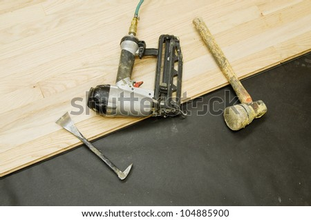 tools for the installation of hardwood flooring on a partly installed wood floor - stock photo
