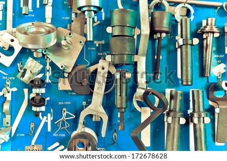 Tools in auto repair garage at wall - stock photo