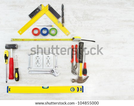 Tools in Shape of House. Home Improving, Repair Concept. White Wooden background - stock photo