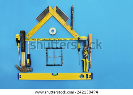 Tools in the shape of house over blue background. Home improvement and Renovation concept. - stock photo
