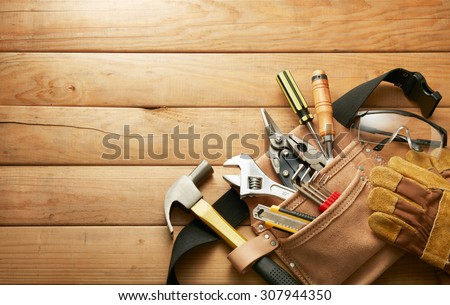 tools in tool belt on wood planks with copy space - stock photo