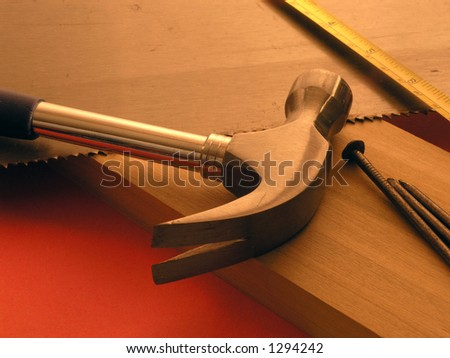 Tools laying on top of cabinet lumber - orange background warm tones