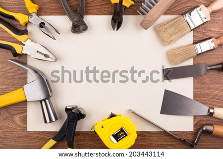 Tools lined up in a circle on a piece of paper. - stock photo