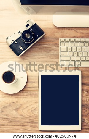 Tools of creativity. Vintage film camera and the latest technology. Elevated view of a photographer / graphic designer desk. High resolution image, vintage post processed, debranded and retouched - stock photo