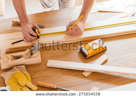 Tools of his trade. Close-up of young male carpenter making measurements on the wooden plank  - stock photo