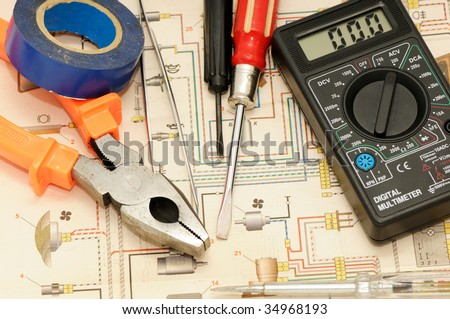 Tools on a background of the electric scheme - stock photo