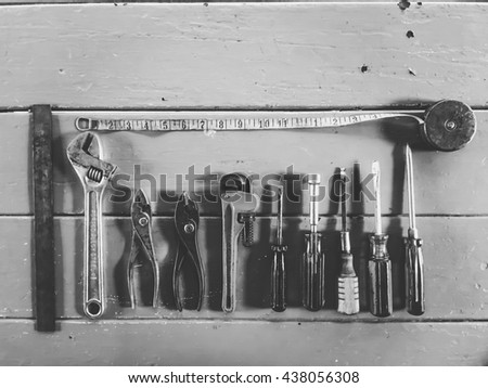 tools on the wood table with wrench tool, screwdriver, ruler and pliers in black and white - stock photo