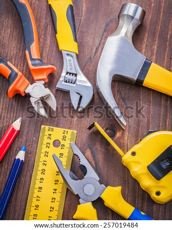 tools on wooden board hammer nippers pliers wrench tapeline ruller pencils
