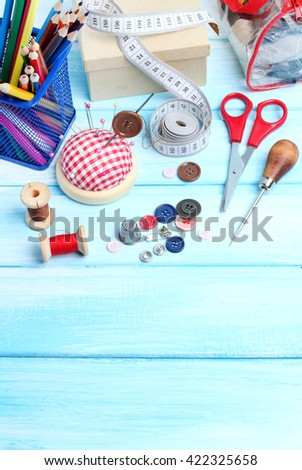 tools tailor spools threads buttons needle sewing blue wooden background - stock photo