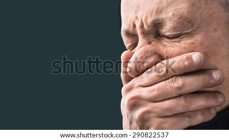 Toothache. Portrait of an elderly man with face closed by hand on dark background with copy-space