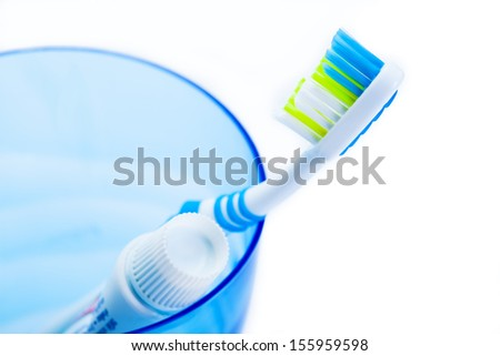 toothbrush and toothpaste in blue plastic glass