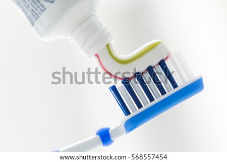 Toothbrush and toothpaste on blurred background with copy space
