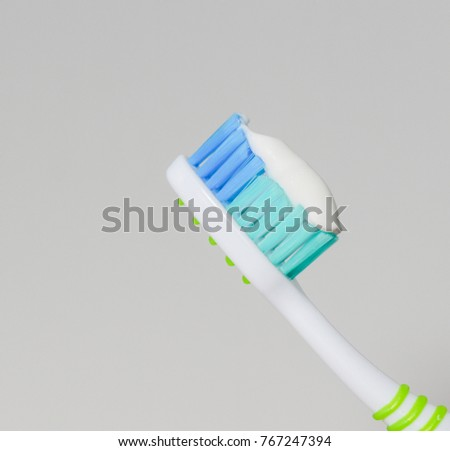 Toothbrush and toothpaste on gray background.