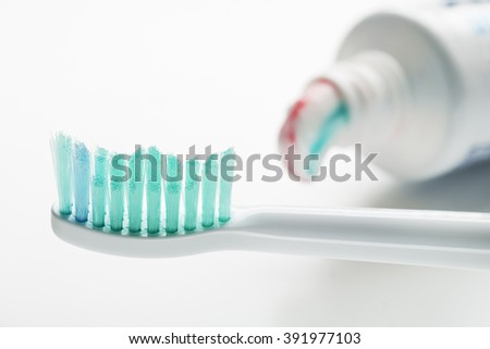 Toothbrush and toothpaste on white background close up.