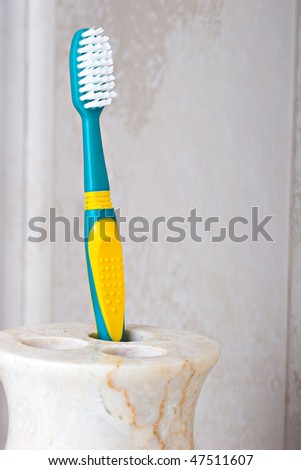 Toothbrush in a marble beige color holder - stock photo