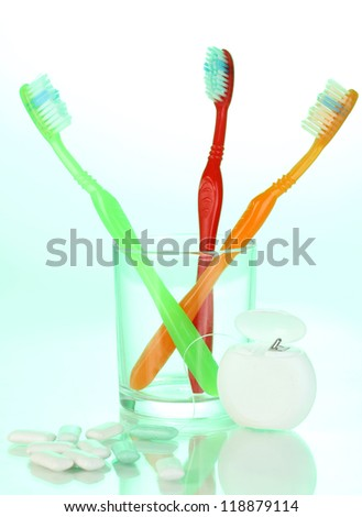 Toothbrush in glass, dental floss and chewing gum on green background - stock photo