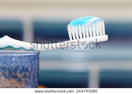 toothbrush with blue toothpaste on a glass - stock photo
