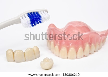 toothbrush with denture, bridge and crown - stock photo