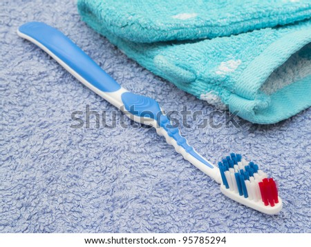 Toothbrush with mitten on bath towel - stock photo