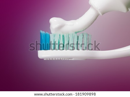 Toothbrush with paste on a violet background - stock photo
