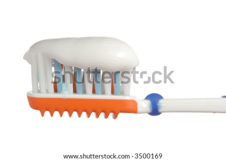 Toothbrush with some toothpaste on it against white background