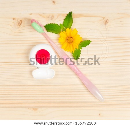 Toothbrush with toothpaste and tooth thread over wooden surface - stock photo