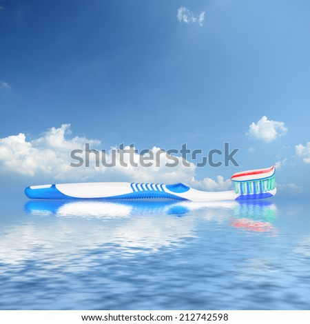 Toothbrush with toothpaste reflecting in water against sky background - stock photo
