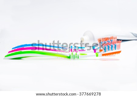 Toothbrushes and toothpaste on white background.