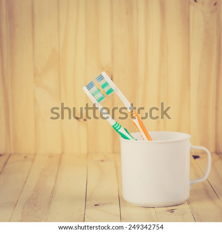Toothbrushes in cup on wooden table with retro filter effect - stock photo