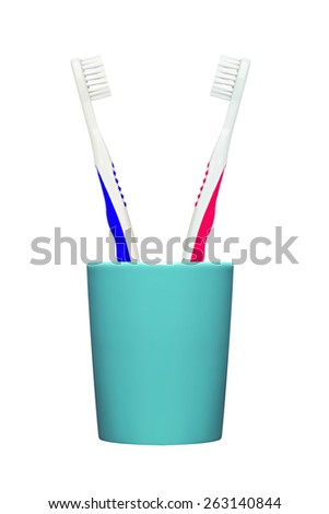 Toothbrushes in glass isolated on white - stock photo