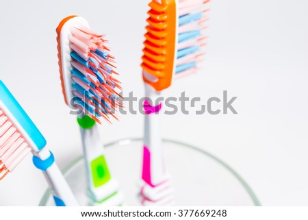 Toothbrushes in glass on white background. - stock photo