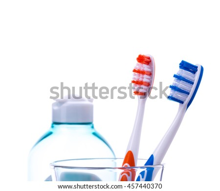 Toothbrushes in water glass with cosmetics bottle isolated on white background. - stock photo