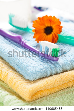 Toothbrushes with toothpaste resting on a pile of fresh towels with a calendula flower - stock photo