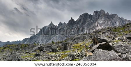 Toothed ridge mountains in cloudy weather in Eastern Siberia - stock photo